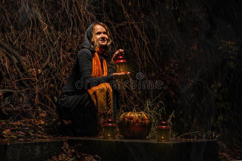 Glückliches Halloween! Eine hübsche Hexe mit einem großen Kürbis Schönes yo lizenzfreies stockbild