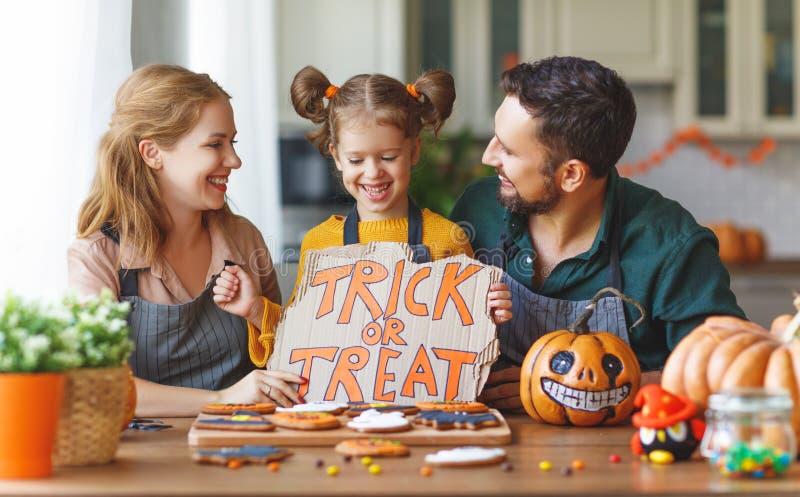 Glückliches Halloween! Familienmutter, -vater und -tochter, die gelesen erhält stockfoto