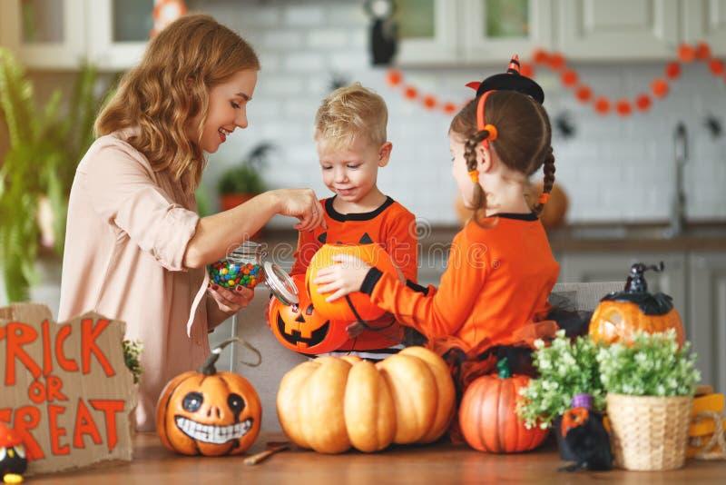 Glückliches Halloween! Mutter behandelt Kinder mit Süßigkeit zu Hause lizenzfreie stockfotografie