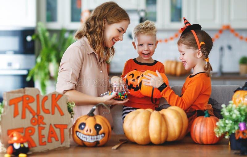 Glückliches Halloween! Mutter behandelt Kinder mit Süßigkeit zu Hause stockfotos