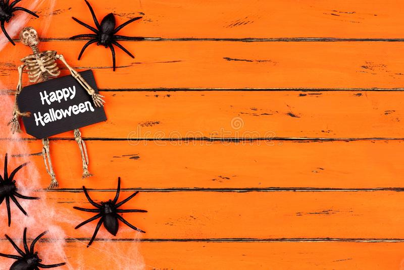Glückliches Halloween-Tag mit Spinnennetz-Seitengrenze auf orange Holz lizenzfreie stockfotografie