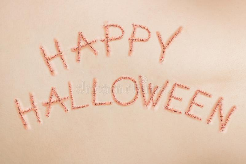Glückliches Halloween-Zeichen, geschrieben in Stiche auf menschliche Haut lizenzfreie stockfotos