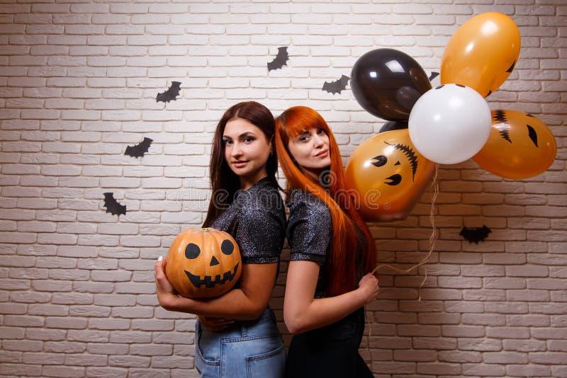 Glückliches Halloween! Zwei junge nette Frauen, die mit Kürbis partying sind und stockfotografie