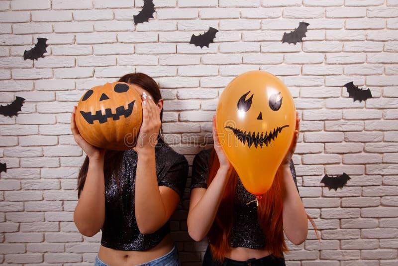 Glückliches Halloween! Zwei junge nette Frauen, die mit Kürbiskopf partying sind lizenzfreie stockbilder