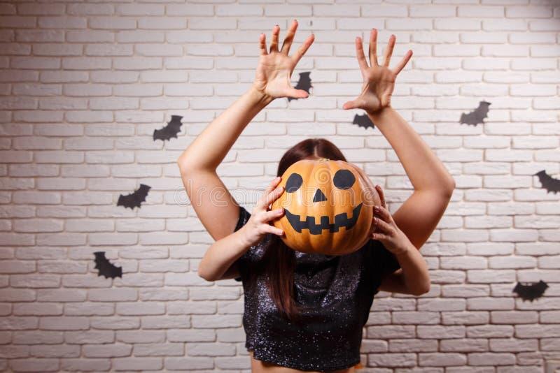 Glückliches Halloween! Zwei junge nette Frauen mit Kürbiskopf erschrecken stockfotos