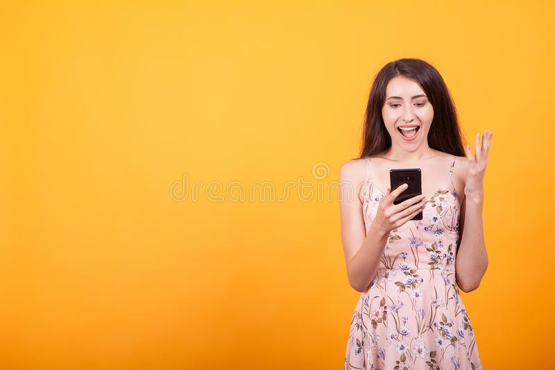Glückliches herausgenommenes hübsches Mädchen im kurzen Kleid, das Handy im Studio über gelbem Hintergrund hält stockfotografie