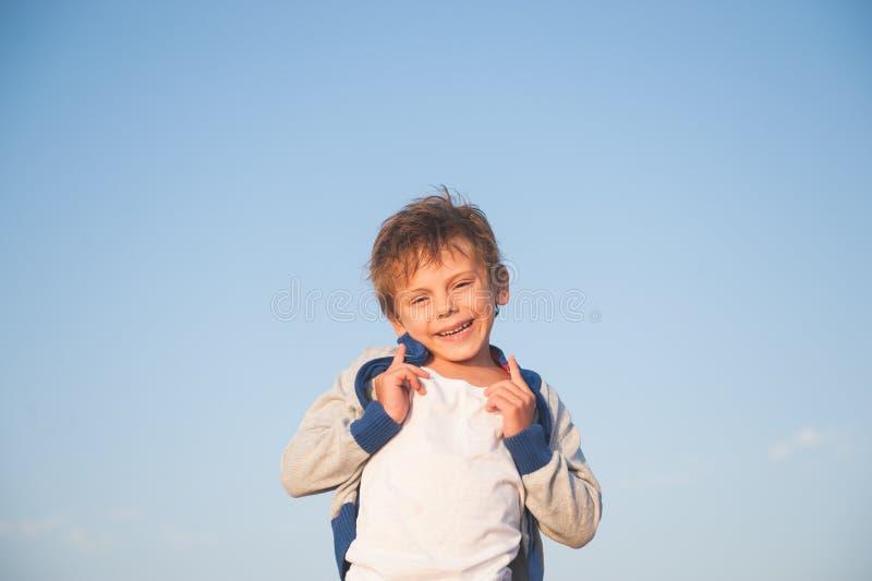 Glückliches herrliches lachendes kleines Kind in der Strickjacke auf Hintergrund des blauen Himmels stockfotografie