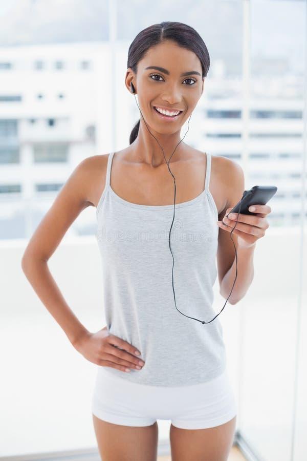 Glückliches herrliches Modell in der Sportkleidung, die Musik hört lizenzfreie stockfotos