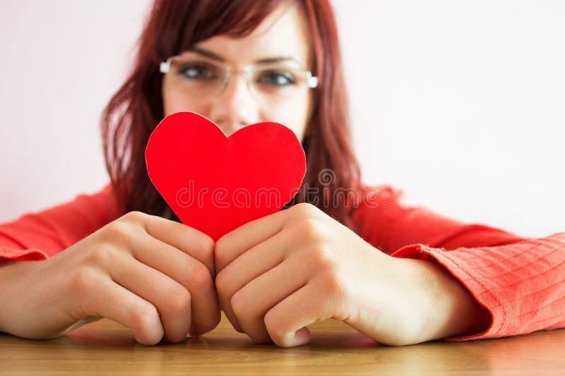 Glückliches Holdinginneres der jungen Frau lizenzfreie stockbilder
