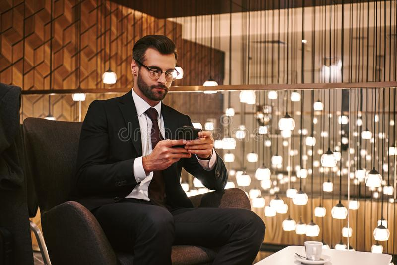 Glückliches Internet Grasens des jungen Mannes auf dem Smartphone, der am Hotelrestaurant sitzt lizenzfreie stockbilder