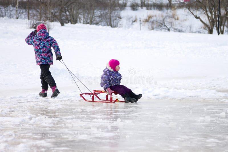 Glückliches ittle Mädchen, das ihre junge Schwester auf einem Schlitten auf dem Eis im Park des verschneiten Winters zieht stockbilder