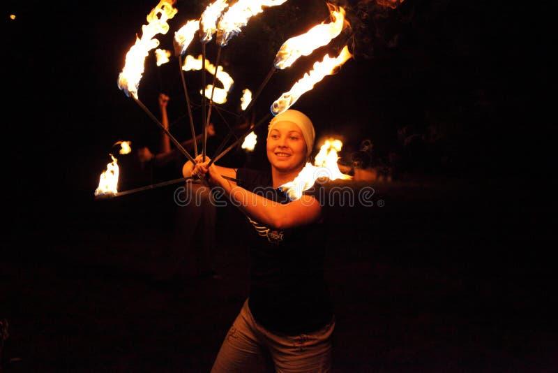 Glückliches Jongleurmädchen, das mit Feuer spielt stockfotografie