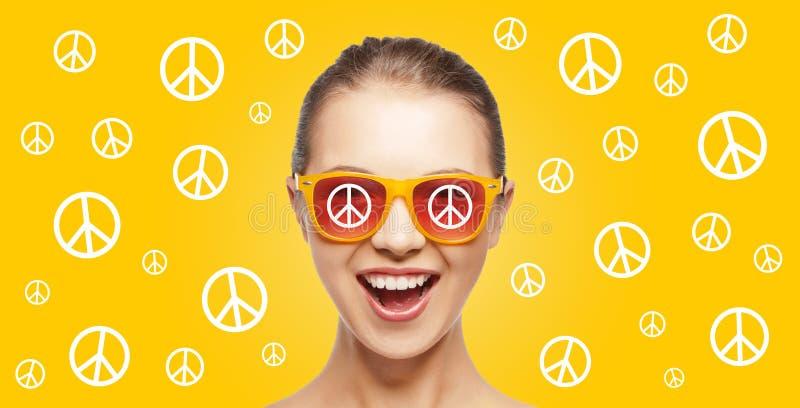 Glückliches Jugendhippiemädchen in den Schatten mit Friedenszeichen stockfotografie