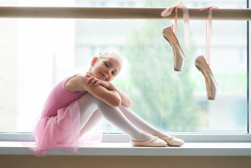 Glückliches jugendlich Ballettmädchen, das auf Fensterbrett sitzt lizenzfreies stockbild