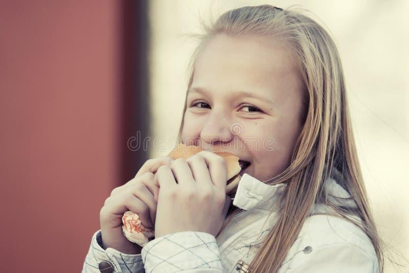 Glückliches jugendlich Mädchen, das einen Burger isst stockfotografie