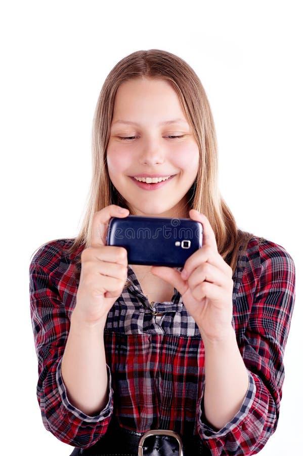 Glückliches jugendlich Mädchenlachen und Gebrauchshandy lizenzfreie stockbilder