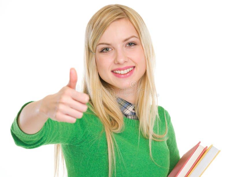 Glückliches Jugendstudentenmädchen, das sich Daumen zeigt lizenzfreie stockfotos