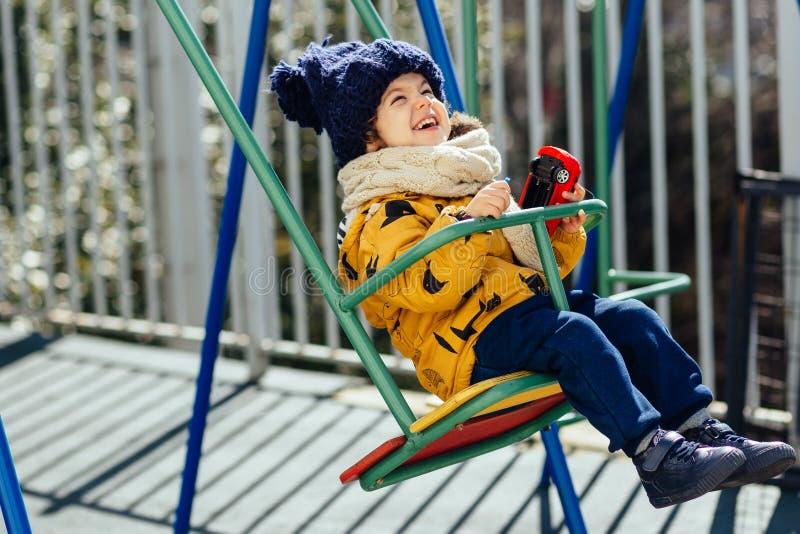 Glückliches Jungenreiten auf einem Schwingen in einem Jackenhut und -schal stockbilder