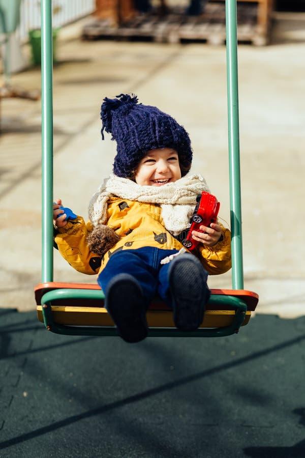 Glückliches Jungenreiten auf einem Schwingen in einem Jackenhut und -schal stockfotos