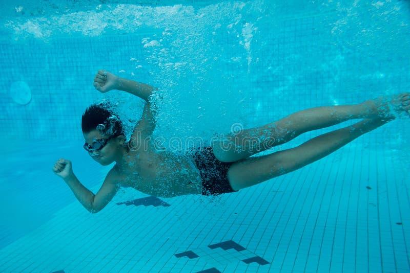 Glückliches junges asiatisches Kind mit den Schwimmenschutzbrillen Unterwasser lizenzfreies stockfoto