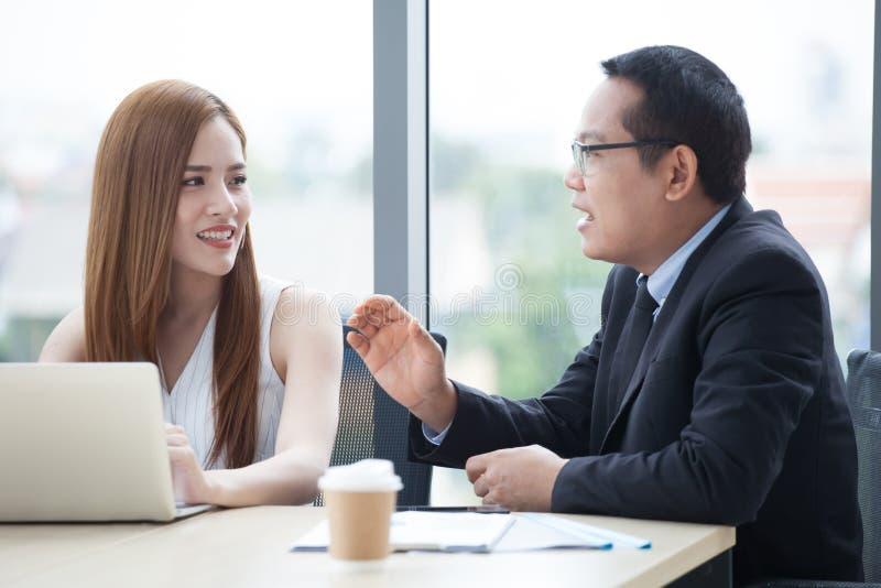 glückliches junges Geschäftsmann- und Geschäftsfrauteam, das zusammen mit Laptop-Computer auf dem Schreibtisch bespricht Informat stockbilder