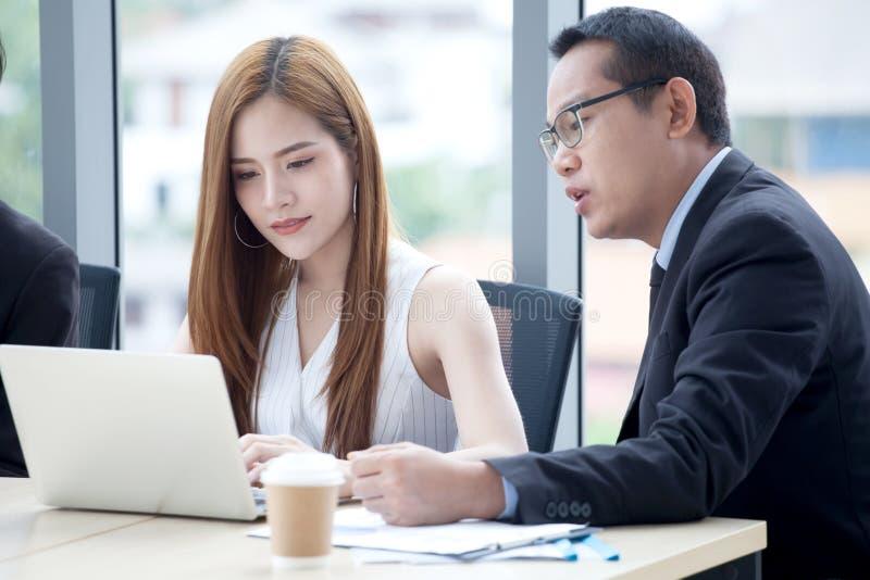 glückliches junges Geschäftsmann- und Geschäftsfrauteam, das zusammen mit Laptop-Computer auf dem Schreibtisch bespricht Informat lizenzfreies stockbild