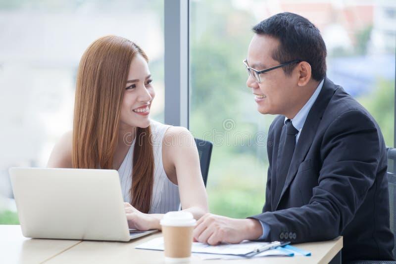 glückliches junges Geschäftsmann- und Geschäftsfrauteam, das zusammen mit Laptop-Computer auf dem Schreibtisch bespricht Informat stockfoto