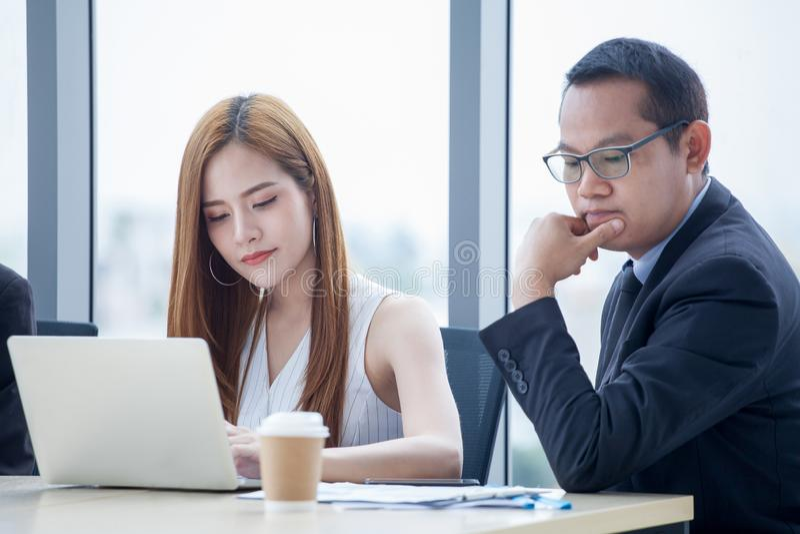 glückliches junges Geschäftsmann- und Geschäftsfrauteam, das zusammen mit Laptop-Computer auf dem Schreibtisch bespricht Informat stockfotografie