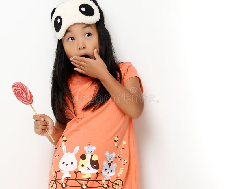 Glückliches junges kleines Kindermädchen mit süßem lollypop überraschte das Betrachten der Ecke lizenzfreie stockbilder