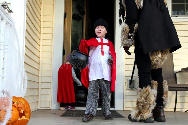 Glückliches junges kostümiertes Kind, das auf Halloween Trick-oder-behandelt lizenzfreie stockfotografie
