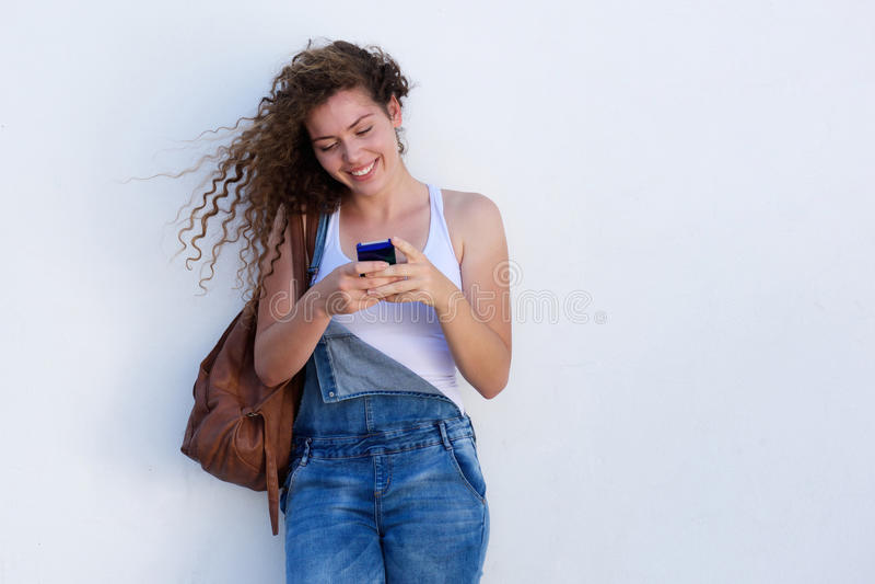 Glückliches junges Mädchen auf dem Mobiltelefonsimsen lizenzfreie stockfotos