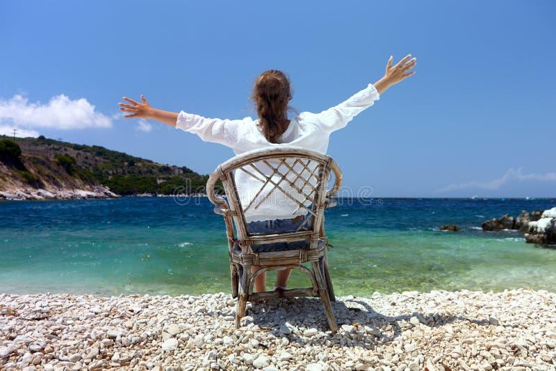 Glückliches junges Mädchen auf einem Hintergrund einer Seelandschaft mit den offenen Händen lizenzfreie stockfotos