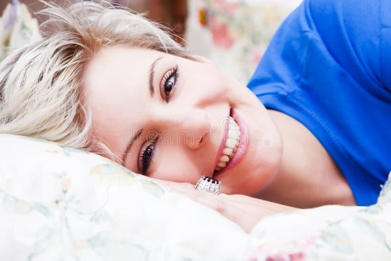 Glückliches junges Mädchen am Bett stockbilder