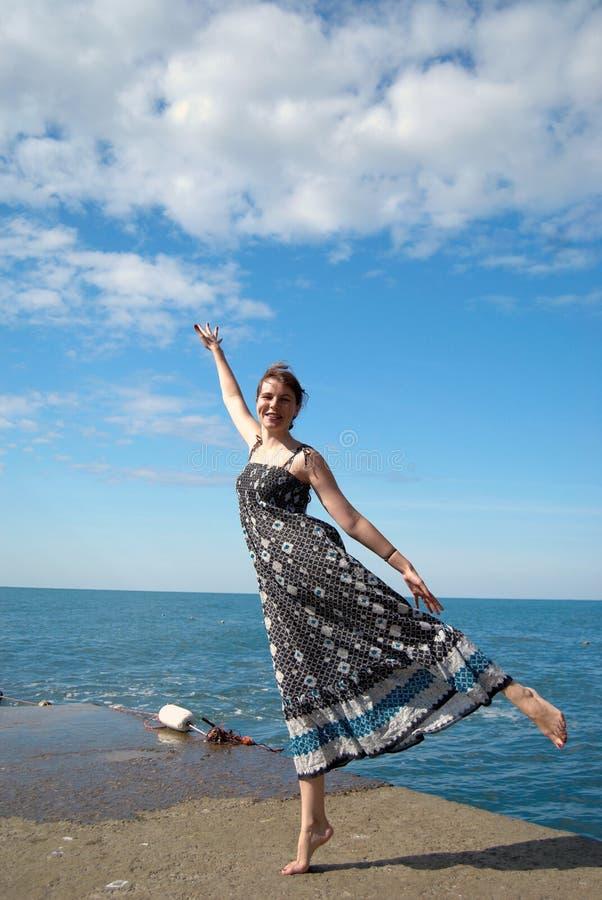Glückliches junges Mädchen, das auf dem Wellenbrecher aufwirft stockbild