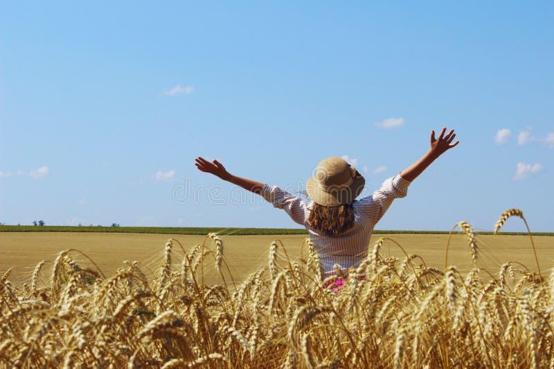 Glückliches junges Mädchen, das auf eine Weizenwiese geht stockfotos