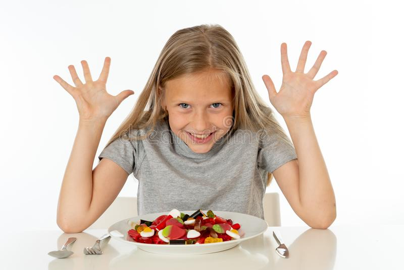 Glückliches junges Mädchen, das eine Platte voll von den Süßigkeitslutschbonbons auf weißem Hintergrund hält stockfotos