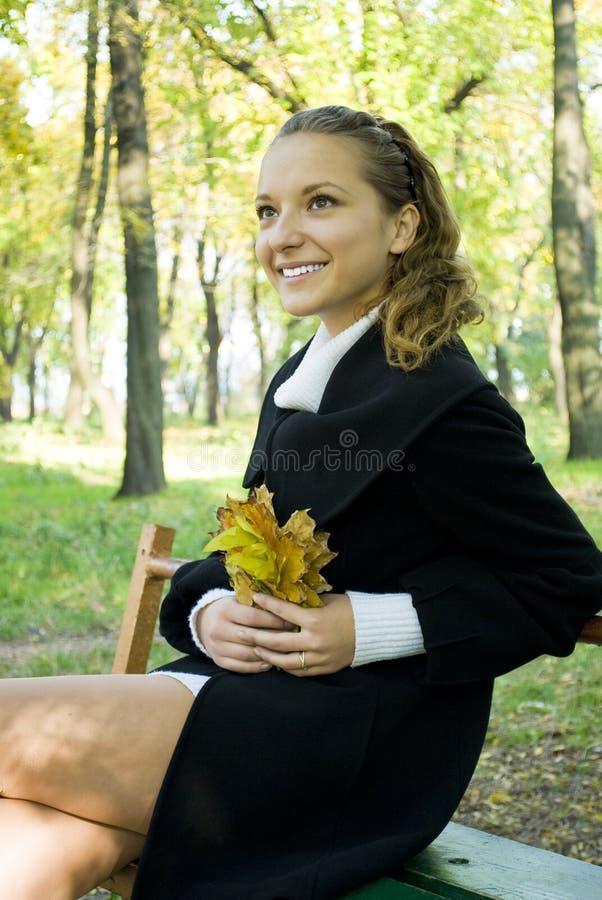 Glückliches junges Mädchen, das Herbst im Park genießt lizenzfreies stockbild