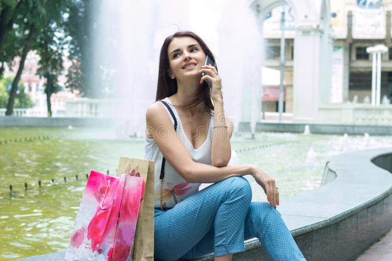 Glückliches junges Mädchen, das nahe dem Brunnen sitzt lizenzfreie stockfotos