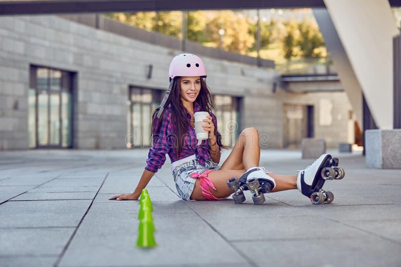 Glückliches junges Mädchen, das Rollschuhlaufen mit Kaffee genießt stockbild