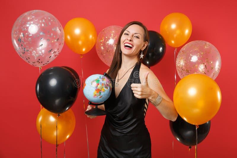 Glückliches junges Mädchen im schwarzen Kleid feiernd, die Weltkugel, Daumen oben auf hellen roten Hintergrundluftballonen zeigen lizenzfreies stockfoto