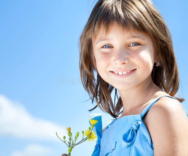 Glückliches junges Mädchen mit einer Blume in seiner Hand lizenzfreies stockbild