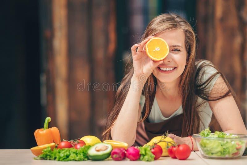 Glückliches junges Mädchen mit einer Orange lizenzfreie stockbilder