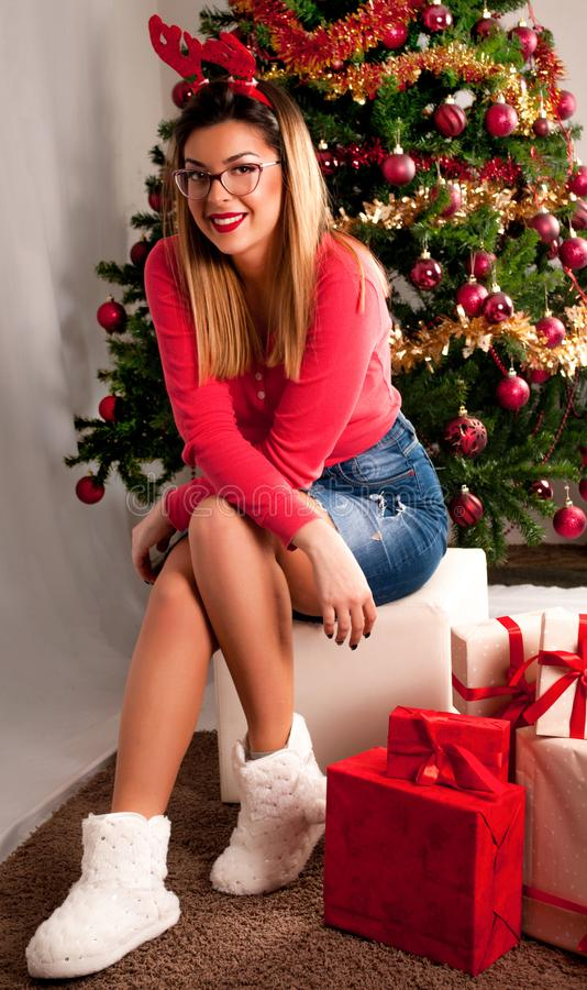 Glückliches junges Mädchen mit Hörnern des Rens und des Rockes, die vor Weihnachtsbaum und Geschenkbox sitzen stockfotografie