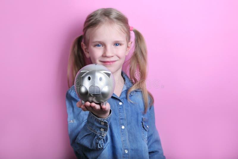 Glückliches junges Mädchen mit silbernem Sparschwein auf rosa Hintergrund Außer Geldkonzept lizenzfreies stockbild