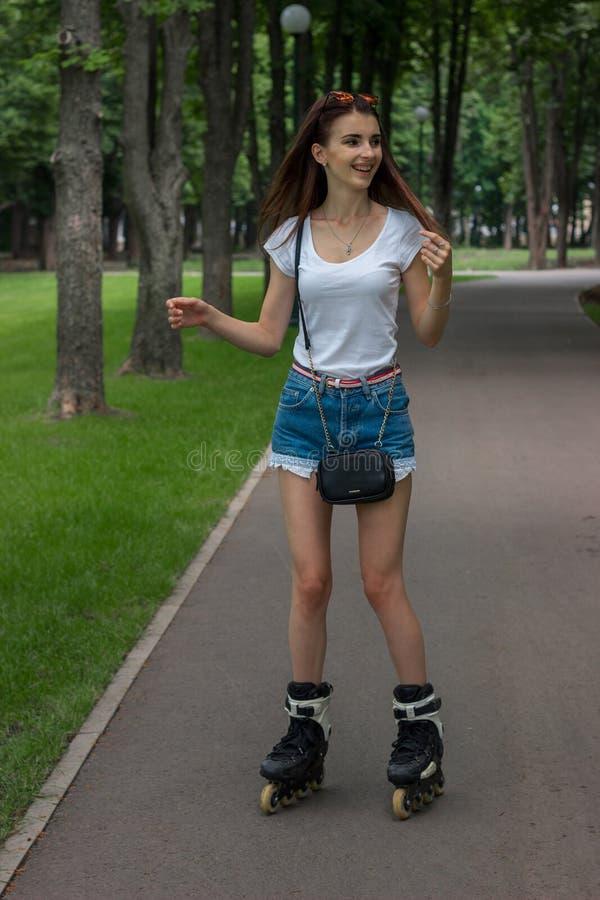 Glückliches junges Mädchenlachen und -rochen auf Rolle am Park stockfotos