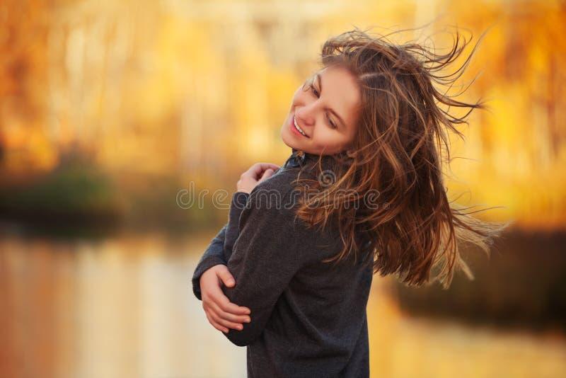 Glückliches junges Modemädchen im schwarzen Pullovergehen im Freien stockbild