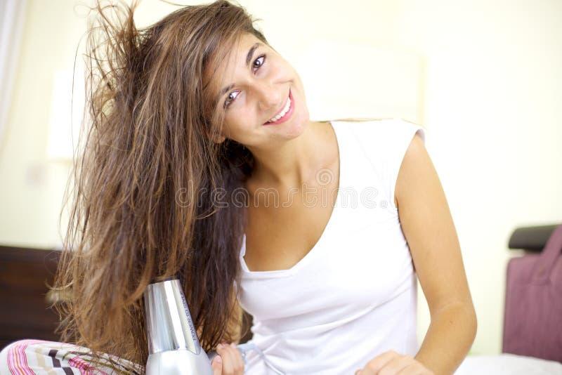Glückliches junges nettes Mädchen, das langes Haar hairdrying ist stockfotos