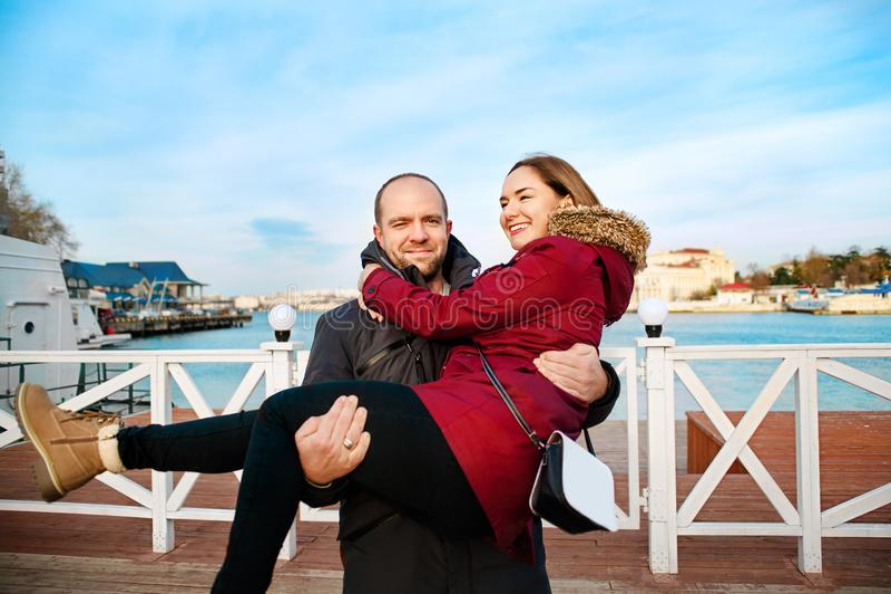 Glückliches junges Paar, beim Liebesumarmen genießt Frühlingstag, der liebevolle Mann, der an hält, übergibt seine Frau, die zusa lizenzfreies stockbild