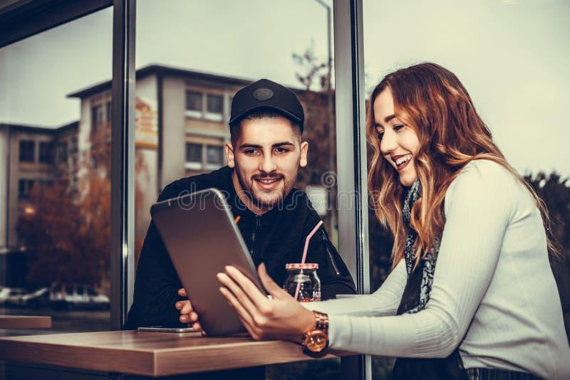 Glückliches junges Paar benutzt eine Tablette lizenzfreies stockfoto