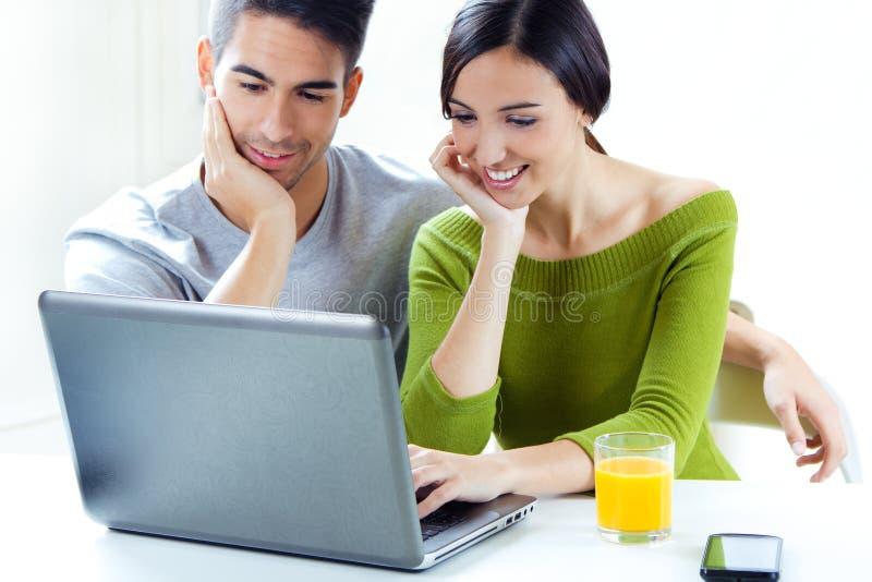 Glückliches junges Paargraseninternet zu Hause lizenzfreies stockfoto